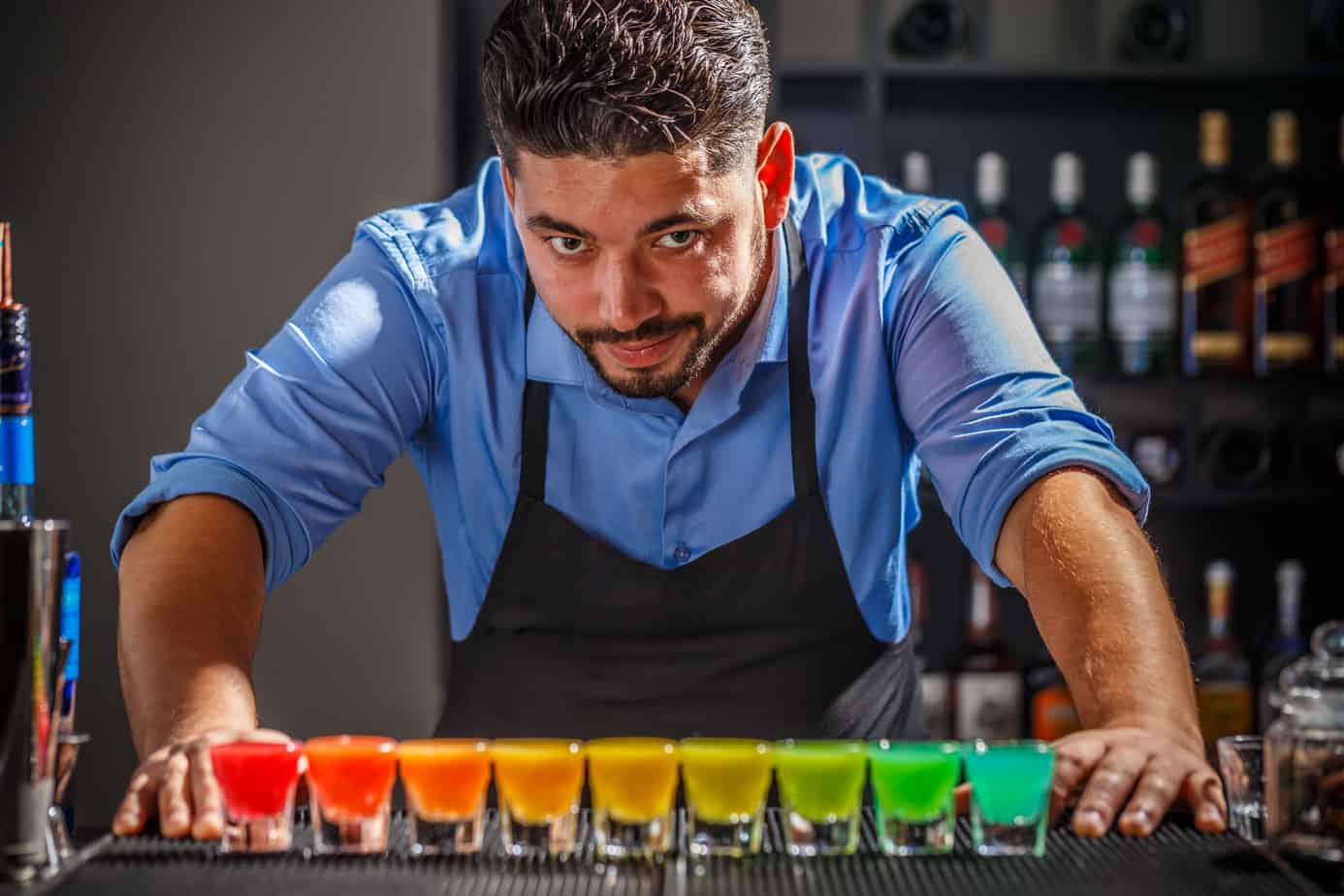 Barman is posing with his rainbow cocktail creation